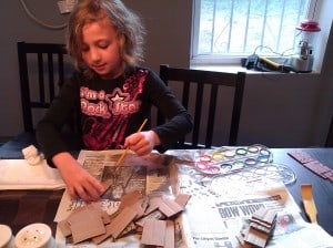 Fiona paints cardboard pieces to look like bricks