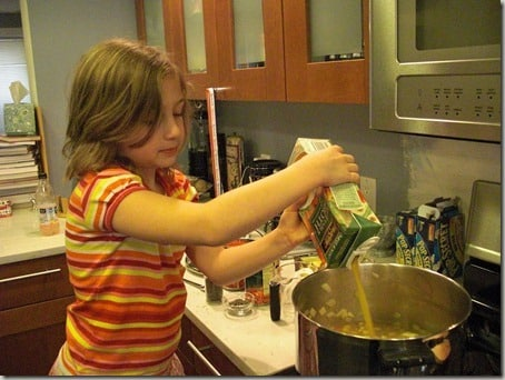 My daughter pouring broth