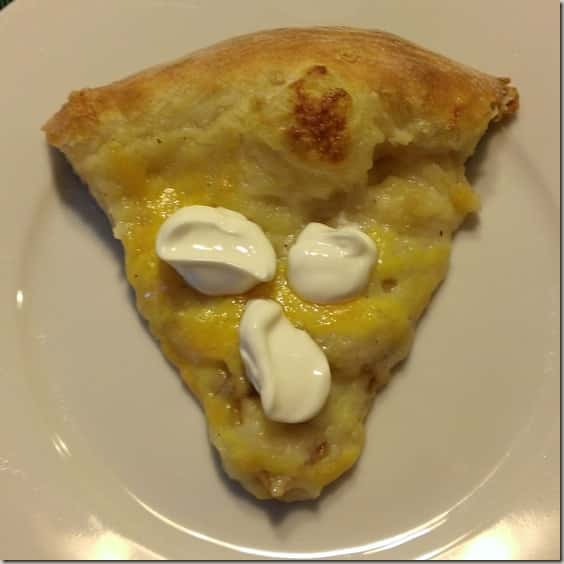 A slice of mashed potato pizza with sour cream