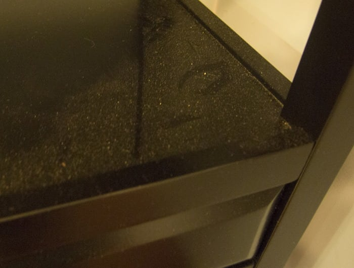 Black shelf with dust, before Clorox Triple Action Dust Wipes.