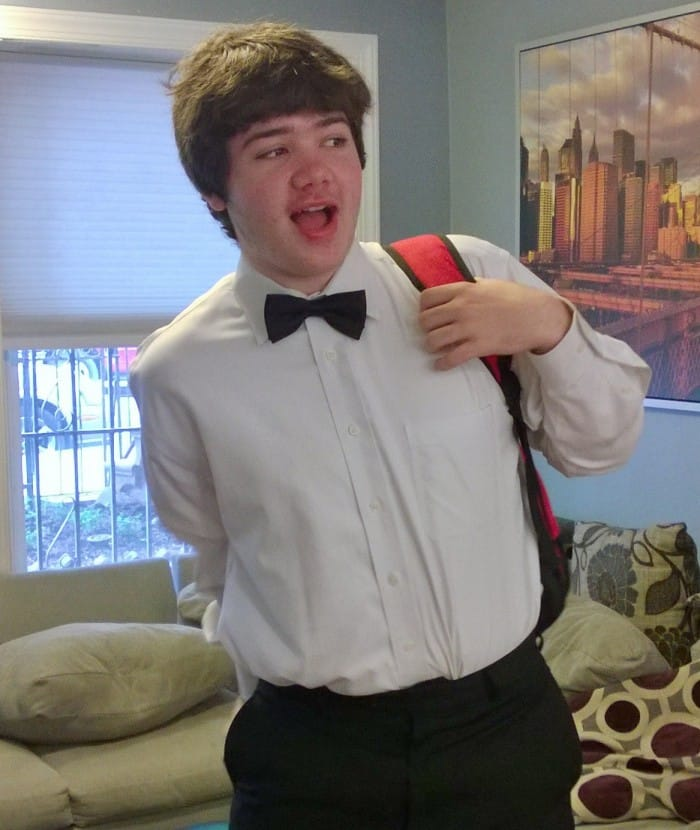 Jake wearing bow tie, putting on backpack.
