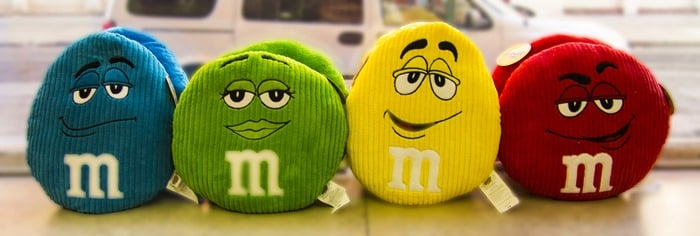 Four M&M's pillows in a row on windowsill