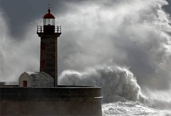 A lighthouse in front of huge, crashing waves and clouds.