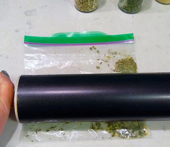 herbs in baggie with a black rolling pin on top