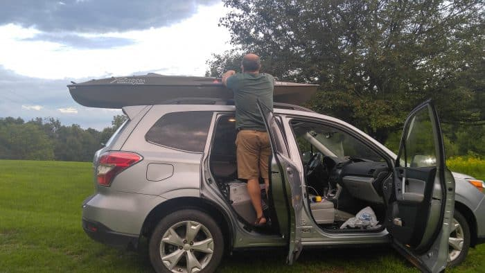 My husband trying to get the kayak off of the top of the car