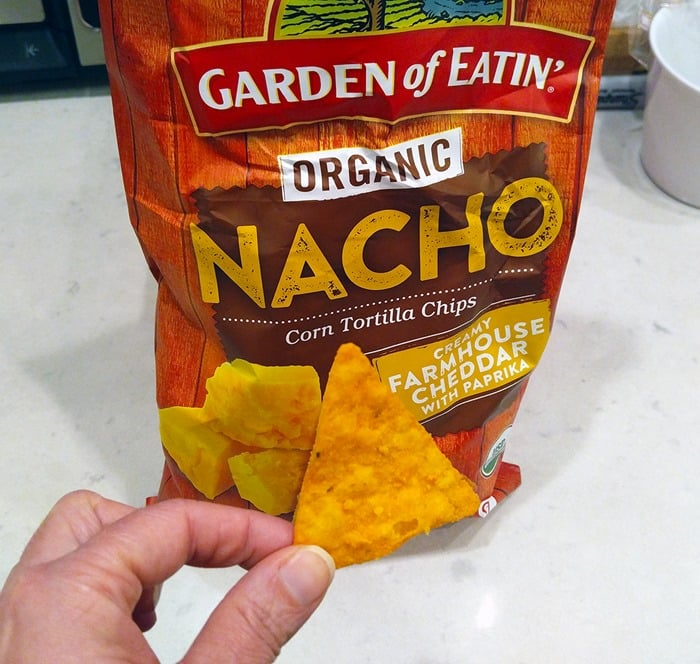 Game Day Babbleboxx - bag of Garden of Eatin' Organic Corn Tortilla Chips, Nacho flavor, with one chip being held in front of the bag