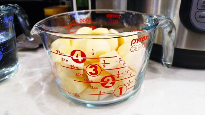 Potatoes for Instant Pot Potato Salad, cut up and in a Pyrex measuring cup