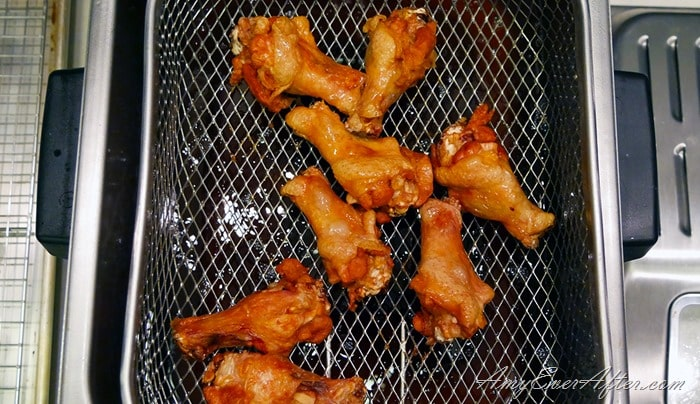 deep-fried Buffalo chicken wings draining into fryer