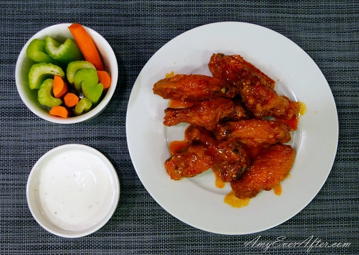 deep-fried Buffalo chicken wings on plate with celery, carrots, and blue cheese dressing