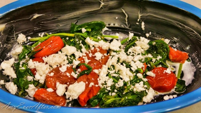 blue dish with tomatoes, spinach, and feta cheese