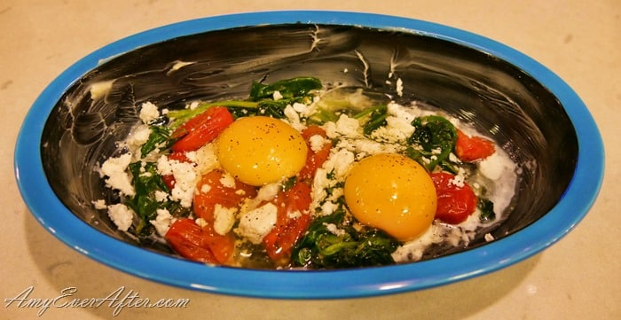 Shirred Eggs - blue dish with tomatoes, spinach, feta cheese, and 2 eggs
