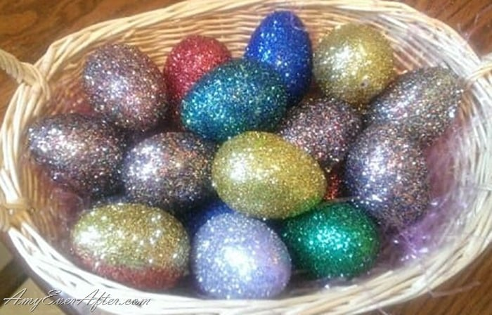 Multi-colored glitter eggs in a basket with light bouncing off of them
