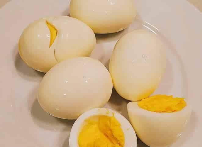 Five hard-boiled eggs on a white, one egg split in half