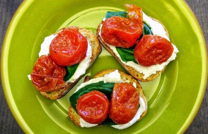 Tomatoes, basil, and ricotta on three thin slices of baguette.