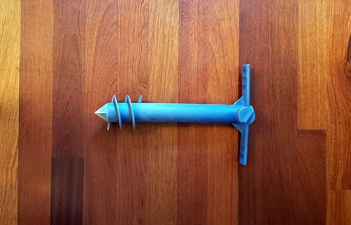 Blue plastic screw that holds a beach umbrella securely in the sand, lying on a wooden floor.