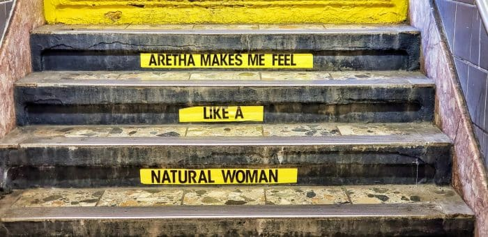 "Yellow signs stuck to the subway steps saying ""Aretha Makes Me Feel Like A Natural Woman"""