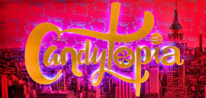 Candytopia sign in yellow script, with NYC in the background
