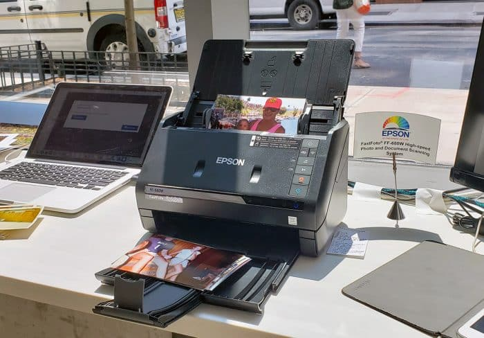 Epson FastFoto FF-680W Photo Scanner on a desk in front of a window with a laptop next to it and pictures loaded into its photo feeder tray.