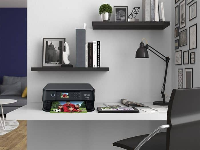 Epson XP-6000 Small-In-One Printer on a desk with a lamp, shelves, and chair.