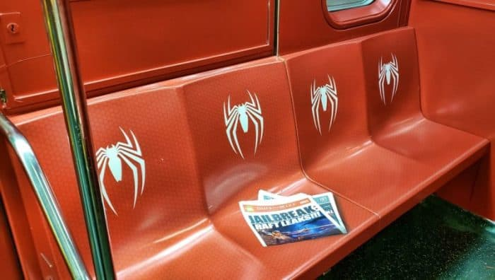 NYC subway car seats painted red with the Spider-Man symbol and a fake Daily Bugle newspaper