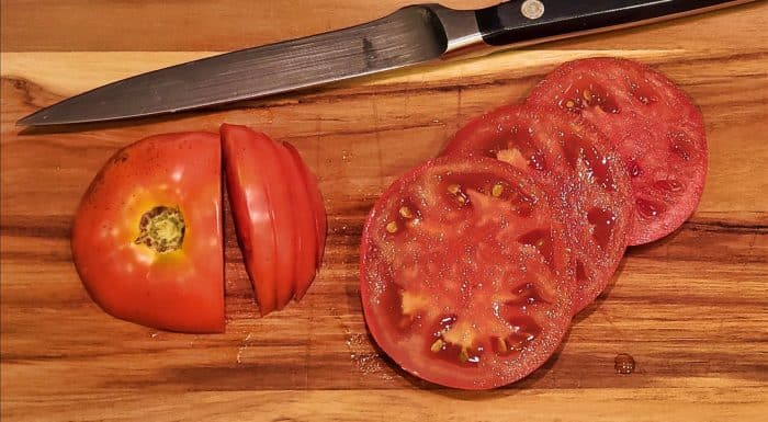 Tomato slices on a wooden cutting board