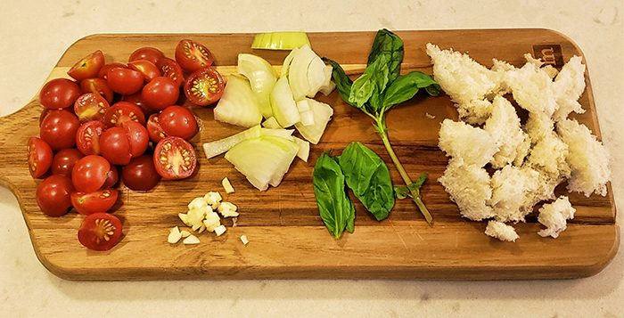 Halved cherry tomatoes, sliced onion, basil, and chunks of bread on a wooden cutting board