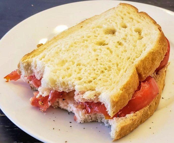 tomato sandwich on white bread on a white plate
