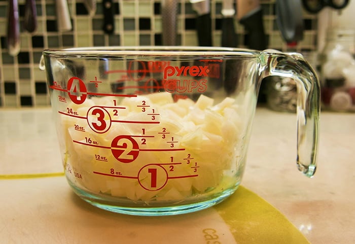 Pyrex measuring cup filled with onions