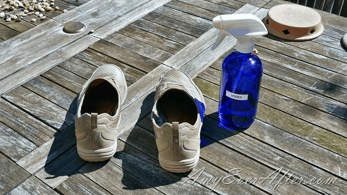 shoes and a blue glass spray bottle of vodka