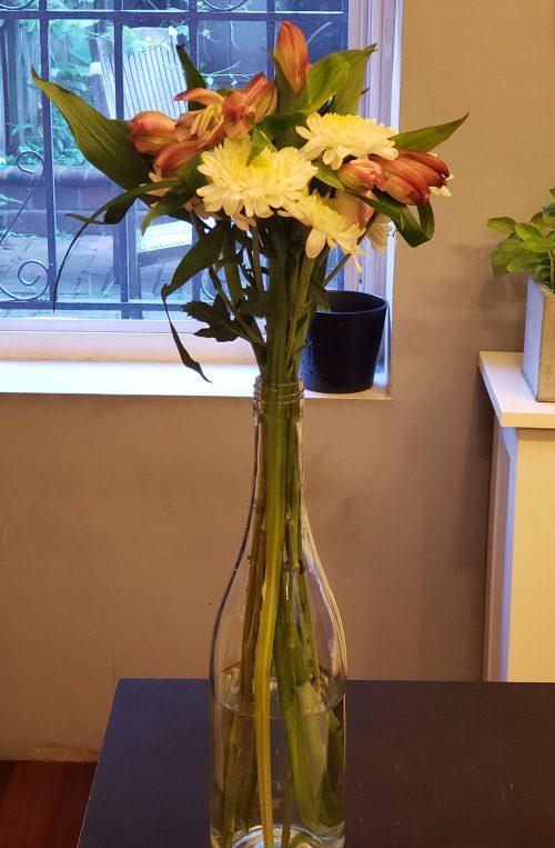 Tall flowers in a wine bottle