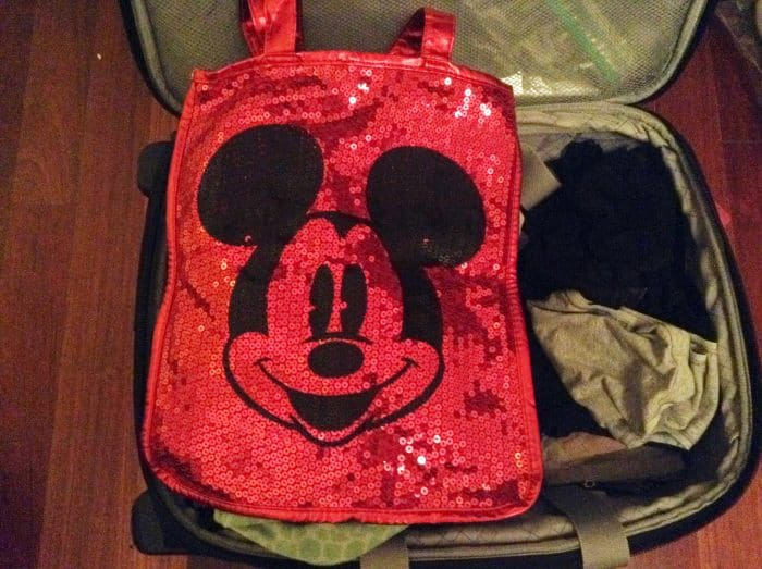 Sparkly red Mickey Mouse bag sitting in a suitcase