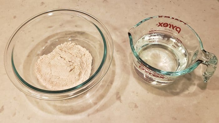 Flour in a glass bowl and water in a glass measuring cup