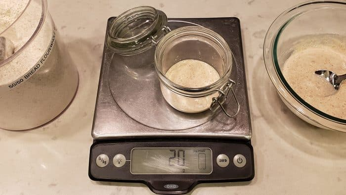 A small jar of sourdough starter on an Oxo food scale